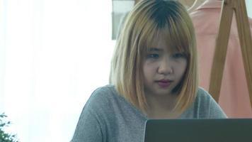 bela jovem sorridente asiática chegando no laptop enquanto está em casa, no escritório com espaço. video