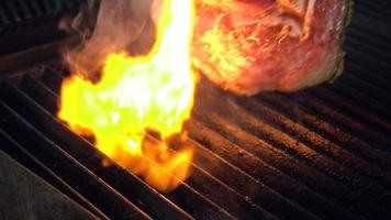 Cooking chief puts uncooked meat piece on hot smoking grill with fire underneath using metal forceps, Close up slow motion.
