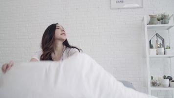 Feliz hermosa mujer asiática se despierta, sonriendo y estirando los brazos en su cama en el dormitorio.