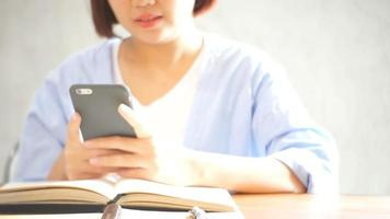 Businesswoman use mobile phone and writing report on wooden table.