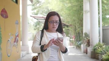 mujer asiática con gafas hablando por teléfono celular mientras camina. video