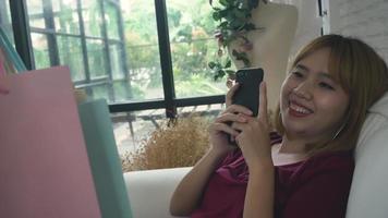 feliz jovem mulher asiática com sacolas de compras em apartamento moderno, verificando a compra. video