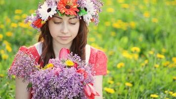 Woman with wreath on head picks lilac and tulip flowers in garden. Happy woman gardener with flowers. Spring and summer. I love to com with plants video