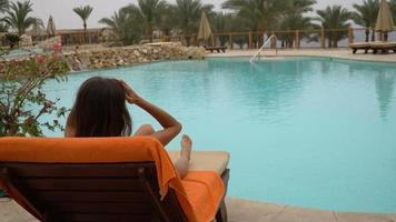bela jovem sentada nas espreguiçadeiras à beira da piscina do hotel