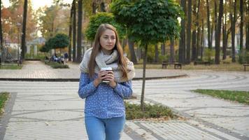 close-up do rosto de uma mulher que bebe chá quente ou café no outono park, ela usa cachecol de malha. menina bebe café de bom humor na caneca