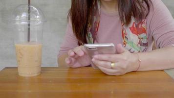 mulher asiática usando smartphone e bebe café frio.