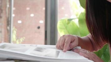 mulher asiática está sentada perto da janela e lendo um livro. video