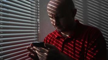 Man in red t-shirt scrolling through information on mobile phone in an office