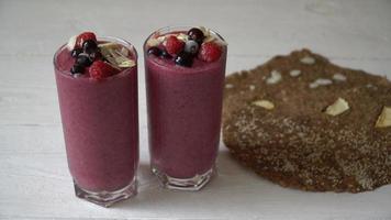 dois copos de milkshake de smoothies de frutas rosa ou smoothie ou coquetel em um fundo branco de madeira.