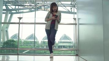 attraktive lässige glückliche junge asiatische Frau im internationalen Flughafen.
