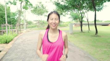Asian runner woman in sports clothing running and jogging on street in urban city park. video