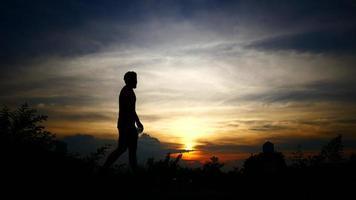 Silhouetten des entspannten Mannes mit dem Hintergrund des Sonnenuntergangshimmels.