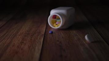 câmera lenta do frasco de comprimidos médicos caindo no chão