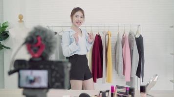 Influencer de moda asiática en línea con bolsas de compras y mucha ropa.