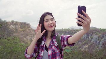Blogger Asian backpacker woman record vlog video on top of mountain.