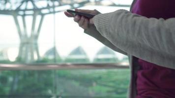 jovem mulher asiática verificando seu smartphone. video