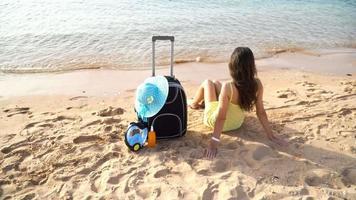 linda mulher sentada com uma mala em uma praia ensolarada
