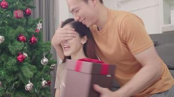 pareja asiática intercambiando regalos de navidad