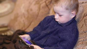 bambino che gioca con il telefono cellulare sul divano