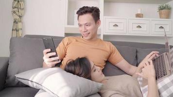 pareja asiática usando dispositivos en casa