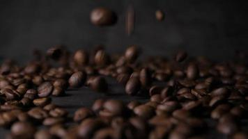 granos de café tostado marrón cayendo sobre una pila