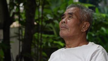 Sad elderly man sitting in the park video