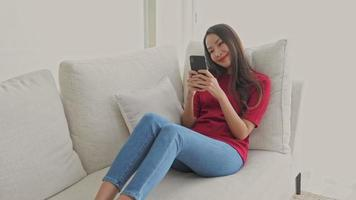 Woman using mobile phone on sofa