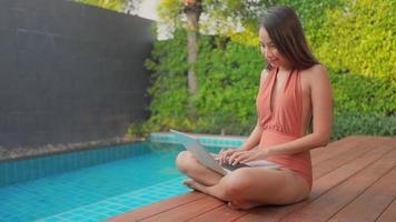 jovem trabalhando em um laptop à beira da piscina video