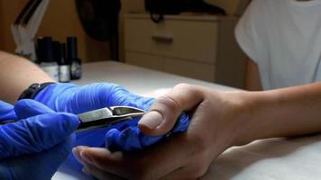 uma manicure corta a cutícula nos dedos da mão de uma garota