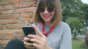 donna asiatica viaggiatore utilizzando smartphone durante un viaggio a ayutthaya, thailandia.