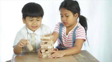 duas crianças jogando um jogo de blocos de madeira no fundo branco,