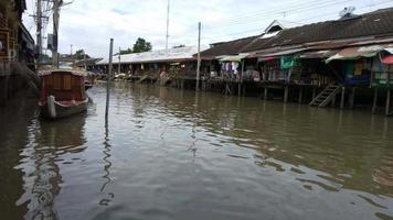 Pueblo y mercado a lo largo de un río con bote de cola larga.