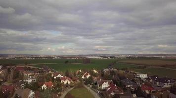 drone voa sobre uma vila em direção às árvores em 4k