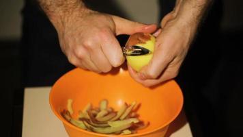 homem descascando batatas na cozinha video