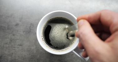Male hand mixing coffee with a spoon