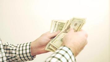 uomo che conta soldi / banconote da un dollaro nelle sue mani 4K