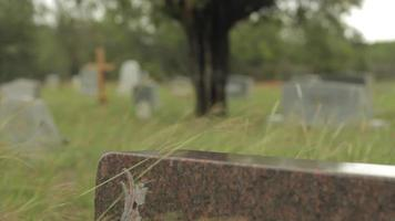 um homem caminha no fundo de um cemitério video