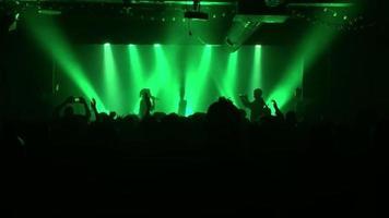 Silhouette von Darstellern auf einer Bühne bei einem Konzert in einem kleinen Club