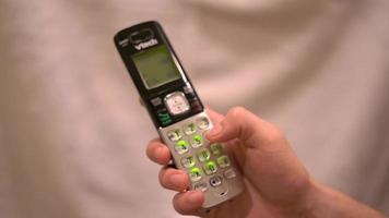 persona que marca el número en un teléfono inalámbrico 4k