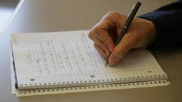filmagem de um homem escrevendo em um caderno