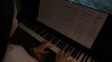 video sobre el hombro de una mujer tocando el piano