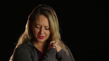 mujer afligida con las manos en el pecho y luego baja las manos