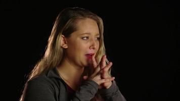 Mujer afligida llevándose las manos a la cara cruzando los dedos de ambas manos video