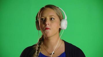 mulher loira mascando chiclete com fones de ouvido