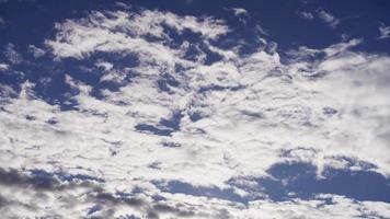 Laps de temps d'un grand groupe de nuages altocumulus se déplaçant de droite à gauche sur un ciel bleu en 4k