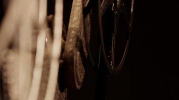 close up de um projetor de filme 8mm, mostrando dois rolos de filme focalizando apenas um no fundo em 4k