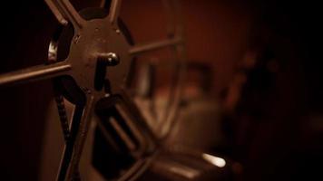 clipe de extremo close-up de um projetor de filme chegando na escuridão com foco em um rolo de filme em primeiro plano em 4k