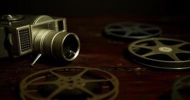panorâmica lenta tomada em superfície de madeira de bobinas, uma câmera e um filme caindo em 4k