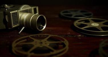 Panoramique sombre tourné sur la table à gauche des bobines, appareil photo classique et bandes de film tombant sur la table en 4k