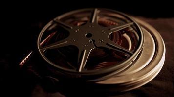 lata de filme com bobina no topo girando em tecido escuro com iluminação do lado direito em 4k